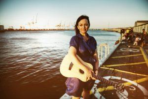 Portraitfoto von Prita mit Gitarre am Meer