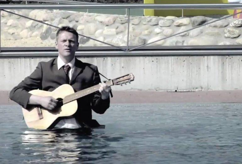 Dirk Schelpmeier mit Guitarre in einem See
