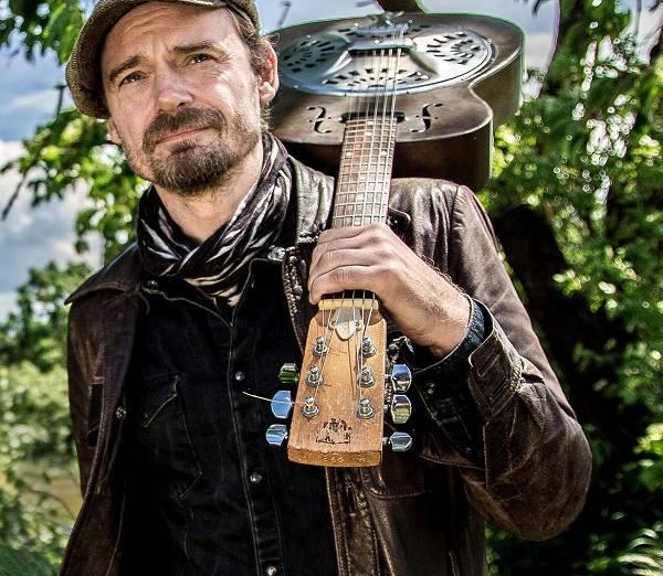 Foto vom Sänger Tim Lothar mit seiner Gitarre auf dem Rücken vor einem Busch