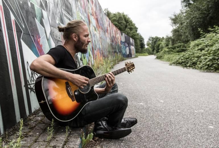 Foto vom Sänger und Songwriter Colbinger auf einer Bank vor einer Mauer